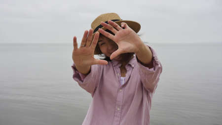 Woman traveler standing on the seashore makes a photo frame with her hands, the distance between the fingers, a photo sign made by the hand of a man. A beautiful Asian woman forms a frame for a photograph with her hands and smiles. The concept of feeling happiness, friendly positive Stock fotó