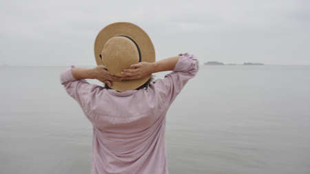 Portrait of a woman traveler against the blue sky. Beautiful Asian woman holds the hat with her hands and enjoys the rest. The concept of feeling happiness, friendly positive. Stock fotó