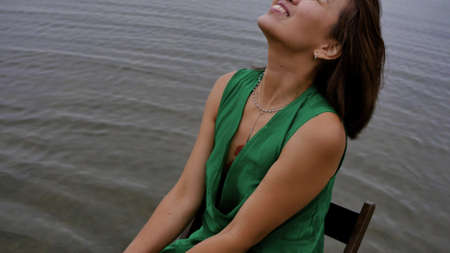 A beautiful Asian woman sits on a chair in the water by the ocean in the early morning and splashes salt water with camla, laughs and poses for a photographer. Happy woman in green dress sits on a chair, relaxes and enjoys lifestyle Stock fotó