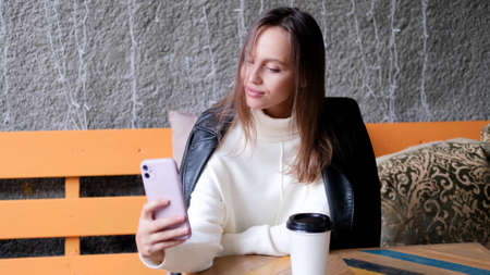 A beautiful woman sits in a cafe and takes a selfie. Casual lifestyle portrait. Businesswoman