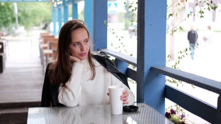 Happy caucasian business woman in a white sweater and black leather jacket drinks coffee on an open veranda in a cafe