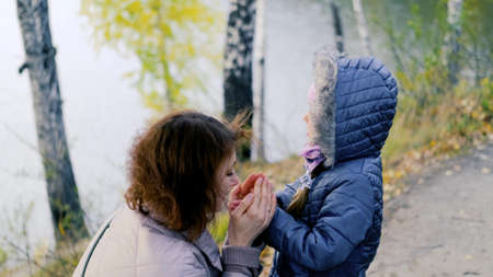 Mom blows on the little girls arms to warm them.