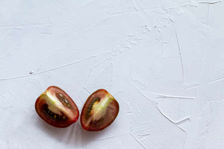 Black delicious tomatoes isolated on gray background Imagens