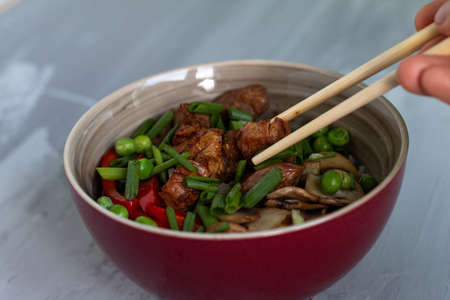 Traditional asian dish with rise and wok roasted meat, vegetables and mushrooms. Top view with space for text