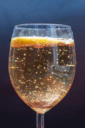 Sparkle lemonade in a glass, dark blue background 写真素材