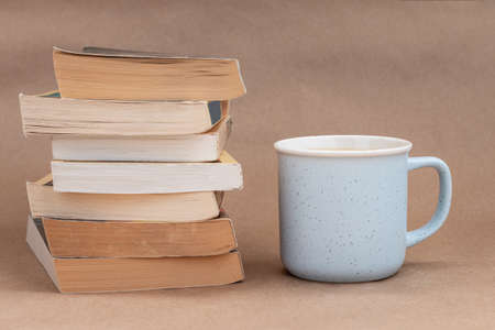 stack of old book with a cup of coffee or tea, beige background