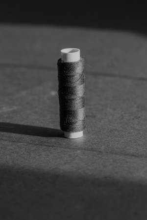 spool of thread in black and white mode. slow fashion and home sewing concept 版權商用圖片