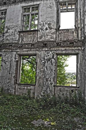 lejano oriente: Ruinas del edificio en mal estado cubierta por vegetaci�n. Hay una gran cantidad de vegetaci�n en el suelo y las paredes del edificio abandonado. La foto fue hecha en un pueblo lejano de Extremo Oriente de Rusia.