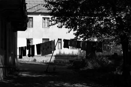 penury: There are linen and clothes that are being aired after washing on the background of shabby house. Photo was made in a distant town of the Far East in Russia.