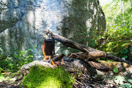 cooking pot: Cooking pot with food on the campfire during hiking.