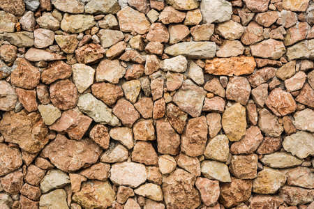 voluminous: Background of massive wall made of bright and colorful stones.