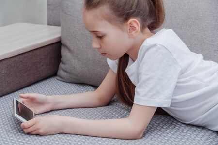 A young girl playing with the phone while lying on the sofa. 스톡 콘텐츠