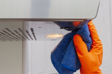 Cleaning domestic cooker hood. Womens hands clean the kitchen hood with a cloth 스톡 콘텐츠