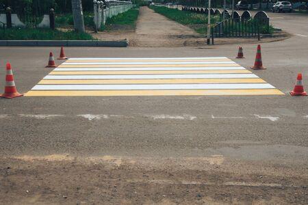 Freshly painted pedestrian crosswalk on the road.