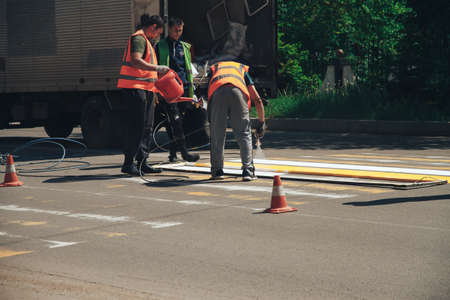 Arsenyev, Russian Federation - May 25, 2020: workers painting a crosswalk