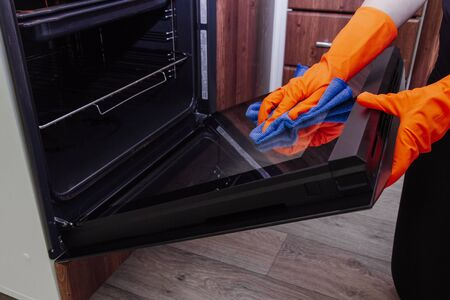 Womens hands in gloves with a microfiber cleaning cloth clean the oven door
