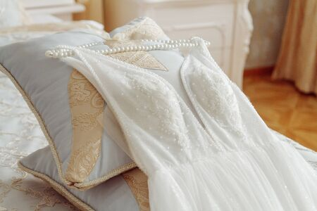 Wedding dress with hanger laying on the bed