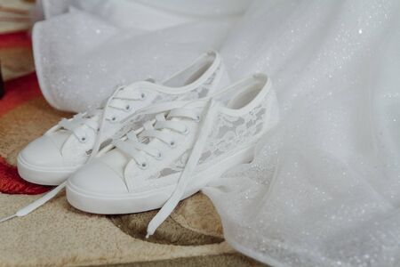 Brides white sneakers are next her wedding dress. Charges of the bride.