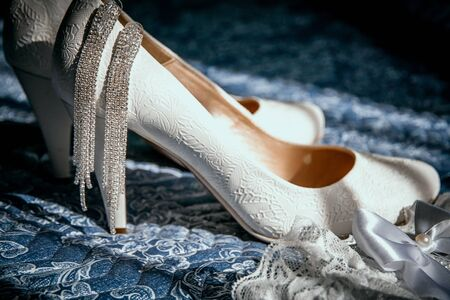 Wedding beige shoes and earrings of the bride in sunlight.
