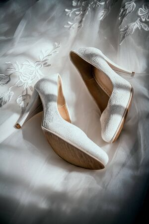 Wedding beige shoes of the bride on the background wedding dress in sunlight.