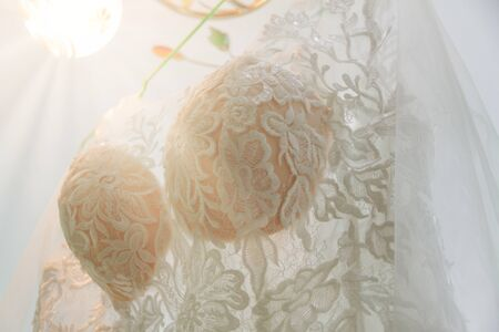 a beautiful lace wedding dress is hanging on a hanger. dress bodice close up. 스톡 콘텐츠