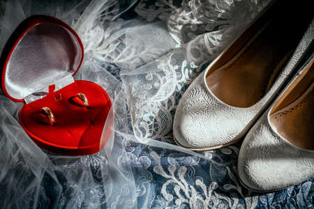 Wedding beige shoes of the bride and wedding rings on the background of a veil