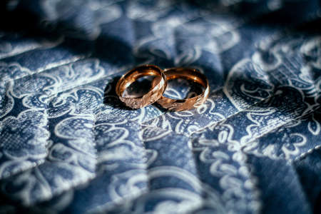 classic gold wedding rings in sunlight with soft bands of shadows