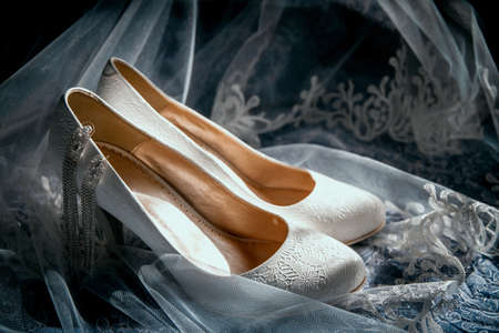 Wedding beige shoes of the bride on the background veil in the sunlight.