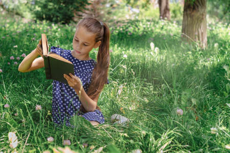 A school-age girl reading a book sitting on the grass in the park. Front view.