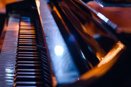 Close-up of piano keys, in the light of evening lights. Soft focus