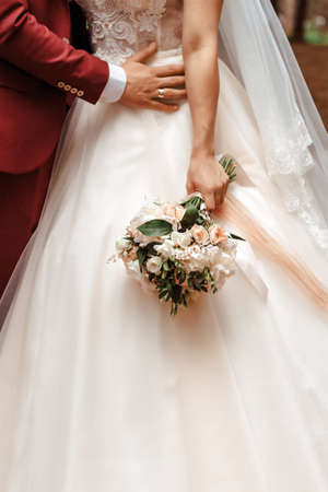 Close-up picture of brides and grooms hands and pink flower rose bouquet. 스톡 콘텐츠
