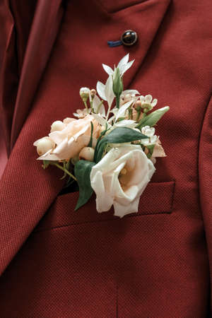 Grooms boutonniere on a maroon suit.