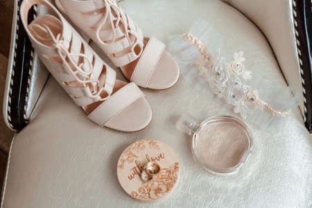 beige shoes for the bride, wedding rings, perfume, garter.