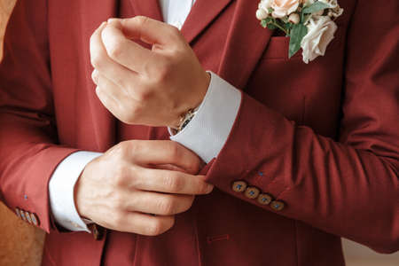 Closeup of a groom in maroon suit correcting a sleeve.
