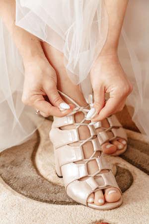 Wedding high heels close up. Bride woman in a wedding dress putting on sandals.