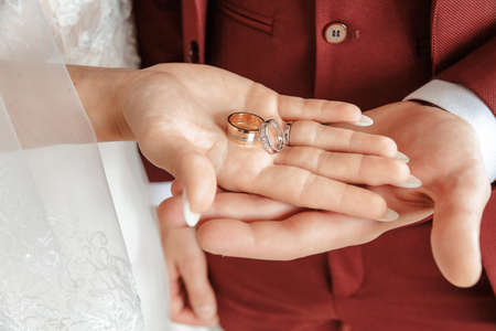 Two wedding rings on bride and grooms palms.