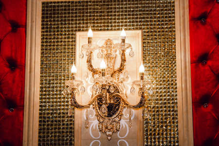 Gold wall lamp with candles in an old classic style.