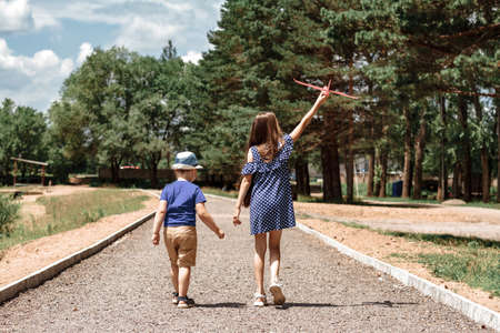 brother and sister go ahead on the road and launch the airplane.