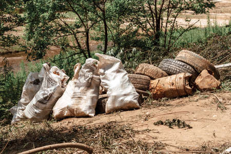 Bagged garbage in nature. Old tires, scrap metal. Nature protection