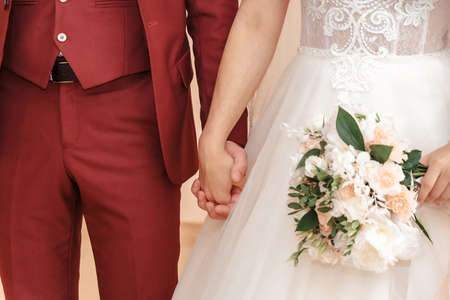 Young married couple holding hands, ceremony wedding day. 스톡 콘텐츠