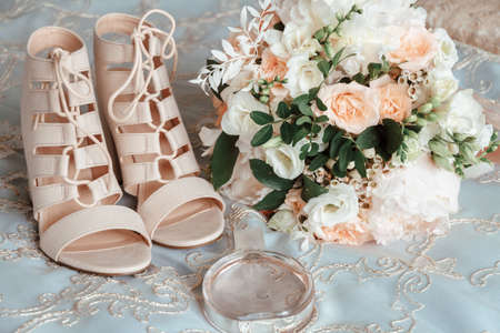 brides bouquet, beige shoes, wedding rings and perfume. The brides accessories