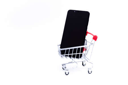 Black mobile phone in a small shopping cart or small cart on a white background.