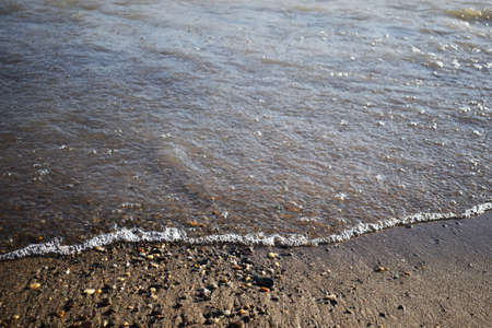 Soft wave of the sea on the sandy beach. pure transparent waves beat on the sandy shore. close-up