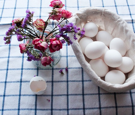 chicken Easter eggs and beautiful spring flowers on a white striped towel lie on the table Banco de Imagens