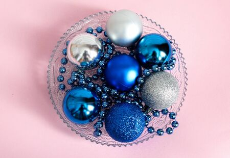 Christmas toys round shape next to the beads, trend color 2020 classic blue, in a plate, on a pale pink color