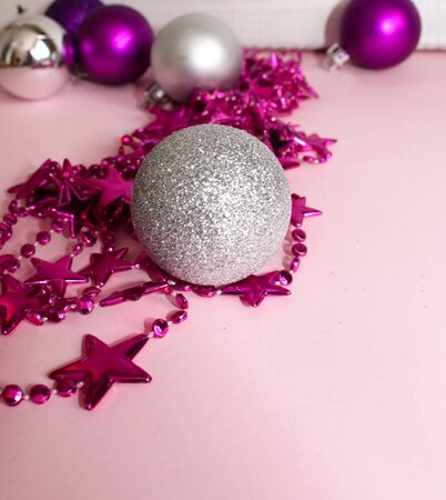 Christmas toys purple on a pink background next to a garland with stars