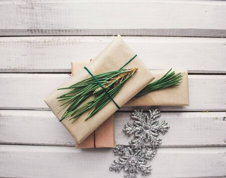 three boxes with Christmas gifts wrapped in Kraft paper, tied with colored threads with fir branches, on a white wooden background with silver snowflakes