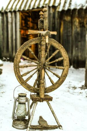 old spinning wheel, which stands on the street, next to the spinning wheel old lantern, historical Antiques Stock Photo