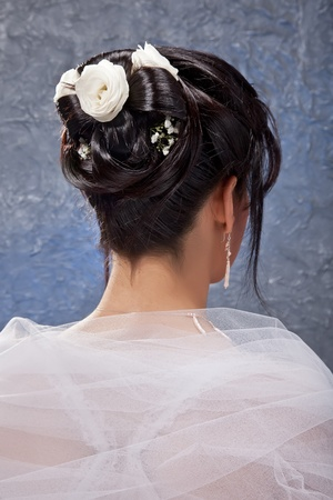 The bride with a beautiful hairdo which inject white flowers. photo