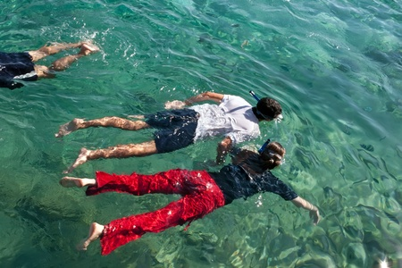 A young man and a woman swimming with snorkeling in the clothes on the red sea  photo